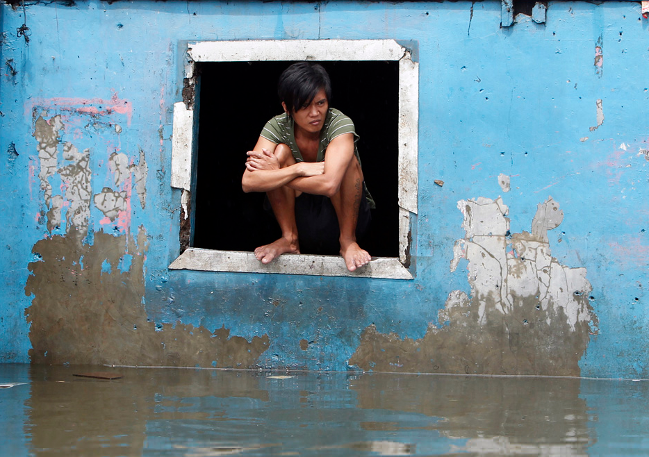 A resident sits on the window of a house swamped with floodwaters in Quezon city, Metro Manila August 8, 2012.REUTERS/Erik De Castro