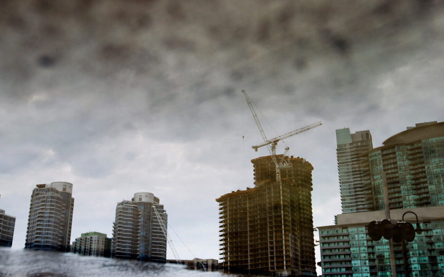 A condo under construction is seen in a reflection in Toronto, Canada, on Aug. 10. Photographer: Brent Lewin/Bloomberg