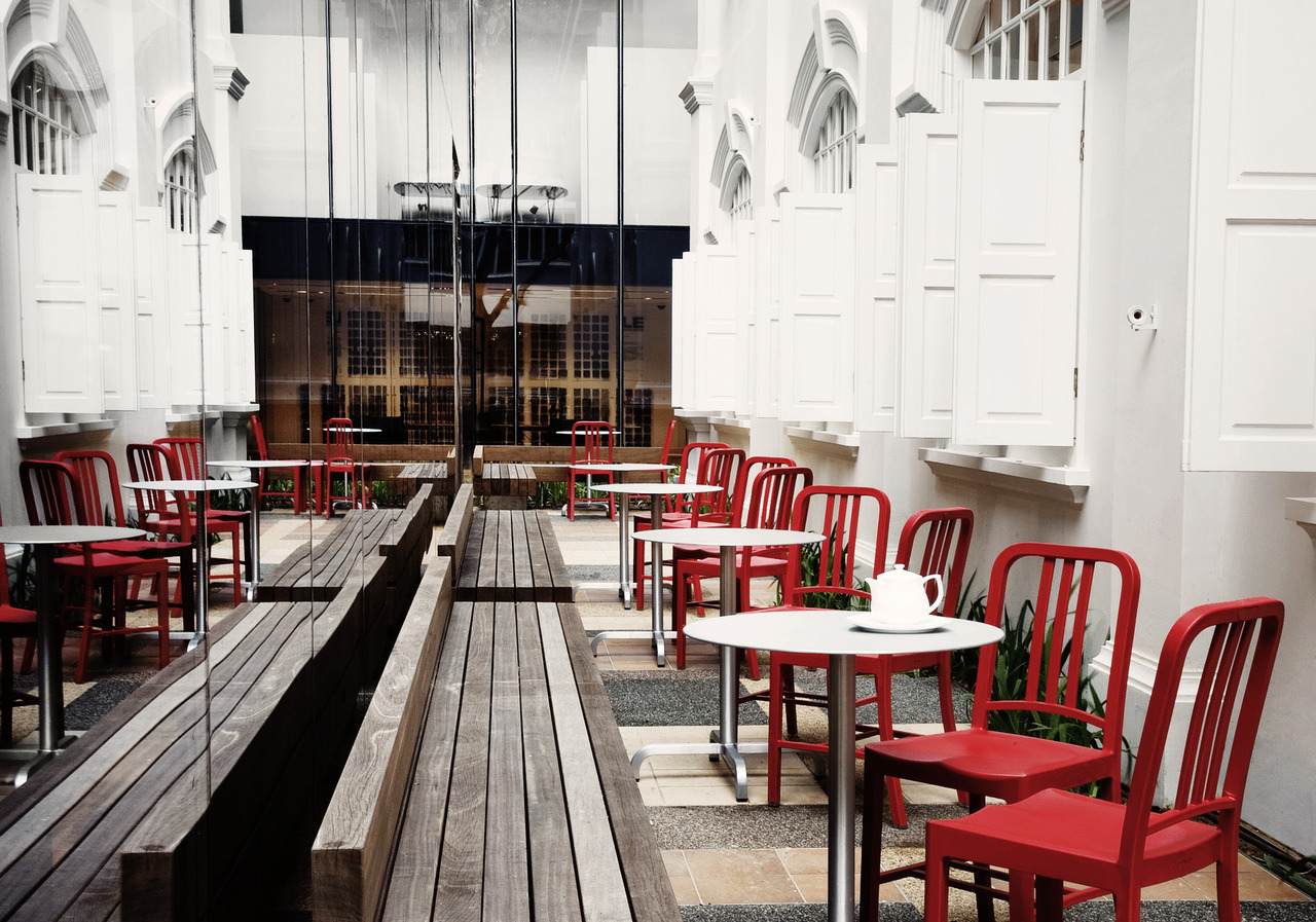 Red 111 Navy chairs at outdoor café within Space Asia Hub, the new flagship showroom designed by WOHA. The retail environment spans 40,000 sq ft across three blocks at Bencoolen street in the midst of the arts and entertainment district of Singapore. All furniture displays in the showroom are complete entities, including the Emeco café with 111 Navy Chairs, made of recycled Coca-Cola bottles. photo by Patrick Bingham-Hall.