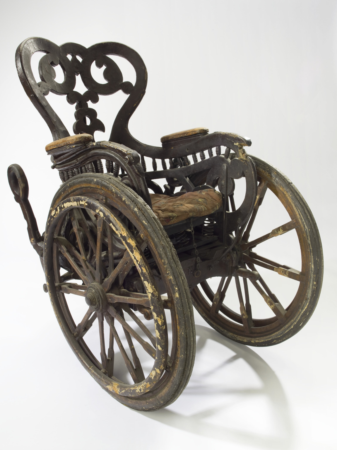Invalid chair, Europe, 1850-1890:Unlike modern wheelchairs that have four wheels, this chair has three: two large front wheels and one small rear wheel. This means the patient was unable to wheel the chair themselves. They would have had an assistant. The chair is heavy so presumably they would not have gone very far or very fast. This elaborately carved chair dates from the late 1800s. It is made of wood with a sprung padded seat. It was donated to the Wellcome Collections by Liverpool Royal infirmary in 1928.
