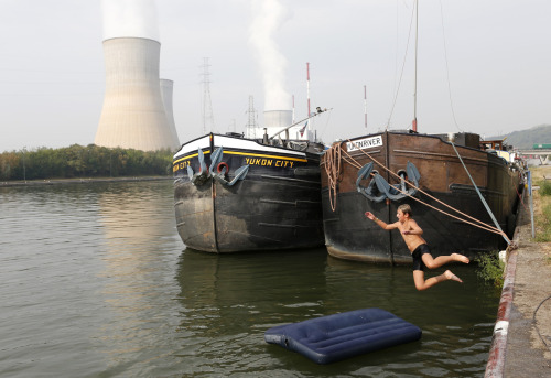 Photo of the Day: A boy jumps into the Hoyoux river as steam billows from the cooling towers of Tihange's nuclear plant. Belgian regulator FANC said the 1,008 MW Tihange 2 reactor in the south of the country would be closed for inspection in September. (Reuters)