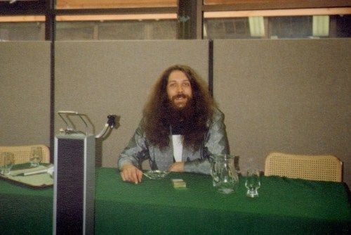 Alan Moore, in his shiny jacket & matching shoes and Mage T-shirt, 1986. Birmingham Comic Art Show 1986 - Motorcycle Museum, NEC, Birmingham, England.