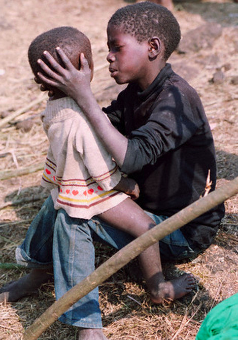 simply-war:  A child cares for another at a refugee camp in Rwanda where people have come to escape the country's civil war. 1994. © David Turnley