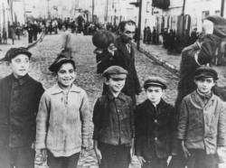 lapetitecole:  Jewish children in the Lublin ghetto. The men behind them were forced to remove their caps in deference to a German officer standing next to the photographer. Poland, 1941–1942. USHMM