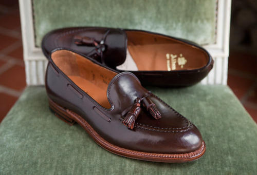 "The Charm of Tassel Loafers I really like tassel loafers. I'm wearing a shell cordovan pair now with brown sharkskin trousers, a dark green v-neck sweater, light blue oxford cloth button-down shirt, navy over-the-calf socks, and a dark reddish-brown alligator belt. With clothes that are a bit too fully cut, tassel loafers can look a little fuddy duddy; with clothes that are too tight, they can look overly hip. Somewhere in the middle, I think, is where they look best. Tassel loafers came into being in the post-war period of the 1940s, right when tweed jackets, Shetland sweaters, and penny loafers dominated prep schools and Ivy League campuses. As college students graduated, they wanted something as comfortable as their slip-ons, but were a bit dressier and more sophisticated for their new life in the business world. It was around this time that an actor named Paul Lukas came back from Europe with a pair of oxfords. They had little tassels at the end of their laces, which Lukas thought made them look more lively. So he took them to a couple of New York shoemakers to see if they could make something similar, and they in turn took the job to Alden. The company's president at the time, Arthur Tarlow, came up with tasseled loafers and they were an instant success. That makes Alden's model the original, and Paul Lukas the first man to wear this style of footwear. You can read more about this wonderful history in this article by Bruce Boyer. Tassel loafers come in a variety of colors and leathers. The most common is brown calfskin, but the ne plus ultra is the reddish-brown shell cordovan that comes from Chicago's Horween Tannery. Shell cordovan has the particularly good quality of holding the color burgundy well. In calf, burgundy can sometimes look cheap, but in horsehide leather, it absolutely glows.  As for where to get them, there are probably a dozens of versions on the market. I'll only cover a few. As mentioned, Alden's is the original and its history as the classic makes it hard to beat. They also make a similar model for Brooks Brothers. The main deviation is the piece of leather that's added to the heel cup. From England, we have Crockett & Jones' Cavendish and Edward Green's Belgravia. Crockett & Jones also makes a shell cordovan version for Ralph Lauren called the the Marlow, and it has a slightly more unique shade of shell cordovan brown. My own pair is Allen Edmonds' Grayson. It's quite similar to Alden's, but it has a higher vamp, which is the part the shoe that covers the top part of your foot. I thought it looked slightly better this way, so I bought a pair in shell cordovan. I couldn't be happier with the purchase and recommend them highly. If you'd like more affordable options, consider Loake's Lincoln and Meermin's 101381. Both come in around $175, but Meermin has the added advantage of being able to do special orders. If you'd like to get a pair in shell cordovan or suede, or made from a different last or sole, they'd be happy to make you a pair for a small surcharge. I have a pair of their made-to-order shoes and couldn't be more impressed with their value. To order, read this buyer's guide and then go to Meermin's website. My only comment on that guide is that you should ask Meermin for sizing advice; don't just assume.  Tassel loafers aren't anything I'd call ""an essential,"" but they're certainly very enjoyable to wear. If you work in an environment that lets you get away with more casual footwear, try wearing a pair of these with a wool sweater and corduroys, or maybe a checkered tweed and flannel wool trousers. Both will carry a great sense of American style that's both casual and sophisticated."