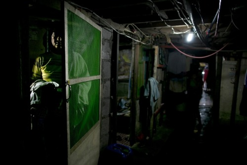 fotojournalismus:  A man stands next to the door of his room under a bridge in Manila on August 21, 2012. Families cram into small rooms under a bridge so they can live for free. Manila's population of 20 million people is rising by approximately a quarter of a million every year. Due to overcrowding a third of the Filipino capital's residents are forced to live on any bit of spare land they can manage, often in makeshift settlements under bridges, beside railway lines and even in cemeteries. [Credit : Paula Bronstein / Getty Images]