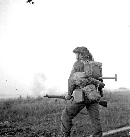 A Canadian soldier near Caen waits for a barrage to clear before advancing; Normandy, France - 25 July 1944