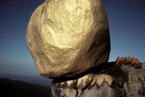 A huge rock, revered by Buddhists and covered in gold leaf, that perches on the edge of a high mountain in Myanmar. Hiroji Kubota shows the sheer magic and power of the rock by cropping off its top. This golden precarious wonder sits dead center against a deep blue sky, its imposing size contrasted with six (small by comparison) crimson-robed priests kneeling to one side of it and the low dark hills below.