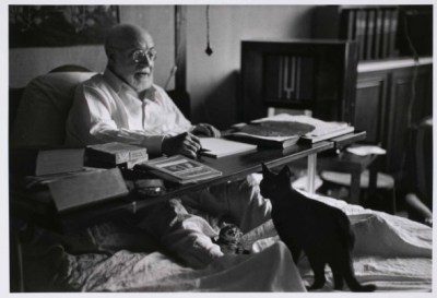 Henri Matisse in bed working, his black cat at his feet, (Cimiez) Nice, France.Robert CapaAugust 1949International Center of Photography, New York, New York, USAIn August 1949, Capa photographed Henri Matisse in his apartment at the Hotel Regina in Nice. At the time Matisse spent much of his time working from his bed on designs for murals for the Chapelle de Rosaire at Vence.