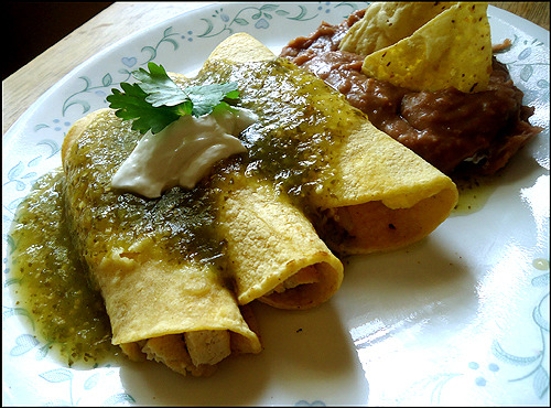 Green Tofu Salsa Enchiladas! Ingredients 1 Tbsp. oil 1/2 onion, thinly sliced 1/2 block extra-firm tofu, drained and cut into strips 1 tsp. minced garlic 1 tsp. cumin 1/2 tsp. salt 1 tsp. chipotle adobo sauce (optional) 6 yellow corn tortillas 1/2 cup mild green salsa 1 Tbsp. vegan sour cream (optional) 1 Tbsp. vegan cheese (optional) Instructions Heat the oil in a pan and add the sliced onions, tofu, garlic, cumin, and salt. If you're using the chipotle adobo sauce, you want to add it now. Let it cook for 5 minutes, or until the tofu is slightly golden.  Warm your tortilla on a separate pan or in the microwave-that way, they're easier to work with. Place a tortilla on a plate and fill with 3 tablespoonfuls of the tofu mixture. Roll the tortilla with the filling and repeat with the remaining tortillas.  Heat the green salsa and pour over the enchiladas. You can top these with vegan sour cream or vegan cheese!  Enjoy!
