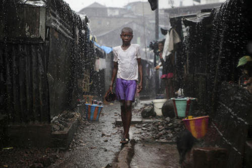 "Photo of the Day: A child stands in pouring rain in the slum of Susan's Bay in Sierra Leone's capital Freetown. Sierra Leone's government has described the current cholera outbreak in the West African state as a ""national emergency.""  At the height of the wet season, over-populated areas with poor water and sanitation are exacerbating the spread of the disease. Some 170 deaths are reported since the start of the year. (Reuters/Simon Akam)"