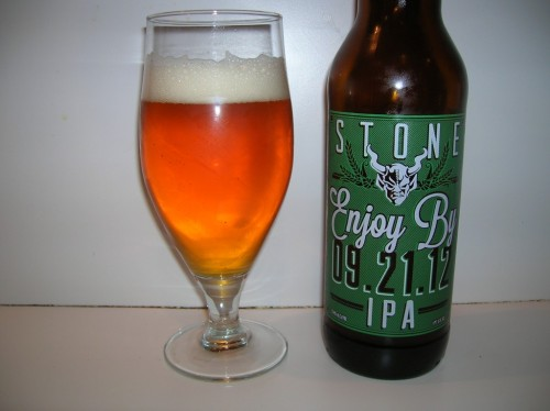 #398: Enjoy By 9.21.12 IPA – Stone Brewing Company, Escondido, California A beer brewed not to last. That's the theme for Stone's latest brew, and it skips subtle branding and goes right for the jugular; it's in the name of the freaking beer. Is this a bad business model? Brewing something with a short shelf life? Is that something to be desired? Apparently it works, because the guy in front of me walked out with six bottles yesterday. It's been released to three markets: Southern California, Chicago, and my beloved home: The Garden State. Freshness is the theme here, and it's a beer with very little in terms of bittering hops and an overload of aroma hops. Super Galena hop extract was used for the bittering end, with Simcoe, Delta and Amarillo used for the aroma addition. Motueka, Citra and Cascade were used in the whirlpool, and it was dry-hopped with Nelson Sauvin and Galaxy. Checks in at 9.4% ABV. The head took a while to mount up on this one, maintaining a patchy, segmented stature for the majority of the pour until the very end, when it finally assumed a foamy, bright white position atop the beer. A pretty beefy chill haze was thrown on the body, so after wiping that away I could see what I'd describe as a burning gold color; orangey glow scattered throughout the body, but mostly golden, with a bright, transparent appearance and subtle carbonation. A riot of hoppiness awaits the nose. You could smell it from a foot away, really. It's a cornucopia of tropical fruit; Very ripe mangos, pineapple, orange, passion fruit, cantaloupe, granny smith apple skins, all thrown into a melting pot of hop power. And upon tasting, that's all certainly there, but I'm absolutely stunned at how bitter this beer isn't. Loading the kettle on aroma hops certainly seems to have given the desired effect. Don't interpret this incorrectly, there's a wealth of bitterness to go around from start to finish. There's a bracing waxy smack up front as the ripe mango flavors greet the palate, revealing a center that's filled to the brim with a myriad of flavors. And I'm so happy to say that malt is one of them. It's still certainly driven by the hops, as you would imagine, but it's less juicy and more biting, like the rind of an orange, or an apple that's been ripe for barely too long. As the beer warms, those harsh ripe fruits turn to watery pineapple and cantaloupe, bit of mango and passion fruit, too. The malt comes up for air at times, quickly being beaten back down by the hops, but it's still there, leveling things out and adding pinches of sweetness. The finish seems tame, but wait for it. It's like a slow burn, as the bitterness will cling to the throat for minutes after your last sip. The Verdict: Quite honestly, this is one of the most enjoyable Double IPAs I've ever had. The lack of assertive and overwhelming bitterness allows you to take in those beautiful hop flavors, while the other parts of the beer bind together to level things out. Punchy, potent, yet balanced. Brilliant and delicious.