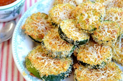 Zucchini Parmesan Bites I made these from a gigantic zucchini that was hiding under a few big leaves in my garden. I somehow overlooked it until it was of monstrous proportions, about 12 inches long and 4-5 inches in diameter.  These little bites are crispy and delicious and I highly recommend this versatile way of cooking zucchini. Once baked, you can layer these with tomato sauce and make zucchini parmesan. You could also cut them into the shape of french fries, instead of circles, in the first step, then crumb coat, bake, and serve with burgers. I like eating them as appetizers with home made ketchup! Yum! Here's how I made these inexpensive and scrumptious treats: Heat oven to 400. Spray a cookie sheet with olive oil spray.  Slice zucchini into 1/4 inch thick circles (or in the shape of french fries), dip in scrambled egg that's been seasoned with salt and pepper. Dredge in bread crumbs that have been seasoned with 1/4 cup parmesan cheese, pinch of celery salt, couple grinds of black pepper, sprinkle of onion powder, shake of garlic powder and 1/2 tsp smoked paprika. Place the zucchini rounds on the cookie sheet, spritz with a little olive oil spray, and top each one with a little fresh grated parmesan cheese. Bake at 400 for 10 minutes, flip each one over, return to oven for 10 more minutes until desired doneness.  Serve with homemade ketchup or marinara sauce.  Yum!