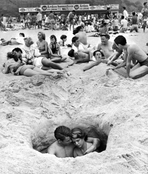 A couple cuddling in a hole on the beach, Santa Monica, 1950. -Ralph Crane