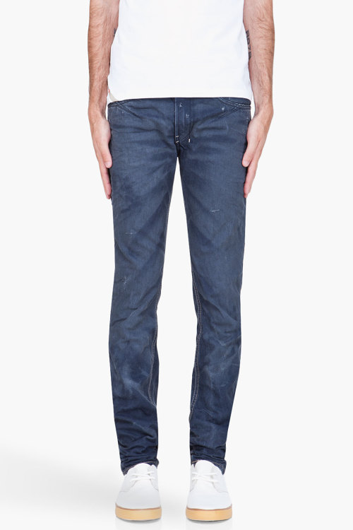 Blue Shioner 801a Jeans by DieselSlim fit jeans in dark blue. Distressing, fading, creasing and white markings throughout. Five pocket styling. Logo flag at coin pocket. Dark blue leather logo patch and green, red and white signature stitching at rear. Contrast stitching in light grey. Zip fly. 100% cotton. Machine wash cold. Made in Italy.