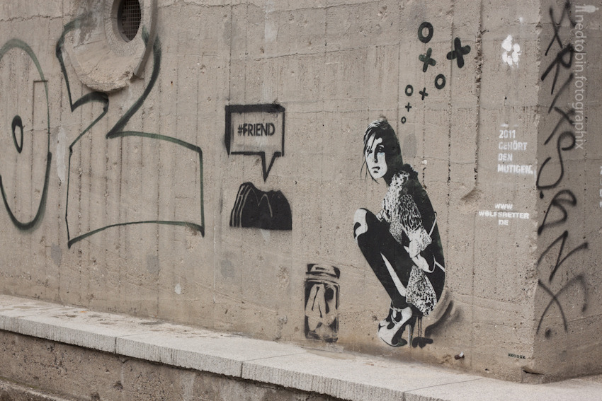 Berlin, Germany. Spray painting of a girl squatting.
