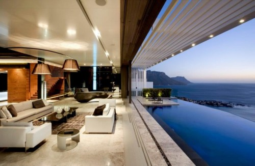 Nettleton 198 by Saota Stefan Antoni Olmesdahl Truen Architects produce an array of amazing homes, and the Nettleton 198 House is another triumph from the design team. The home is filled with style surprises, such as an aqua themed hallway, suspended staircase and open-air living. The entire home can be opened up to the warm breeze thanks to its disappearing walls, and a full scale eight seated dining set is located right in the center of the central garden for unobstructed alfresco dining under the sun, moon and stars. Perched high over Clifton, the beautifully modern home is flanked on the east edge by a hillside garden, whilst the western aspect looks out over the expansive Atlantic Ocean, visible from a huge sun patio, generous living space and a master bedroom with a retractable glass perimeter. A glossy black kitchen forms a solid base note at the heart of the lightly decorated home, creating a sumptuous cooking zone full of drama and sophistication, a superb area to show off ones serious culinary skills to a gathering of discerning guests. With a roof situated sun terrace and a smooth cool infinity pool, this is an amazing home for entertaining–day or night–or a place in which you can take sanctuary away from all the hustle and bustle, and never want to leave! All photos courtesy of: