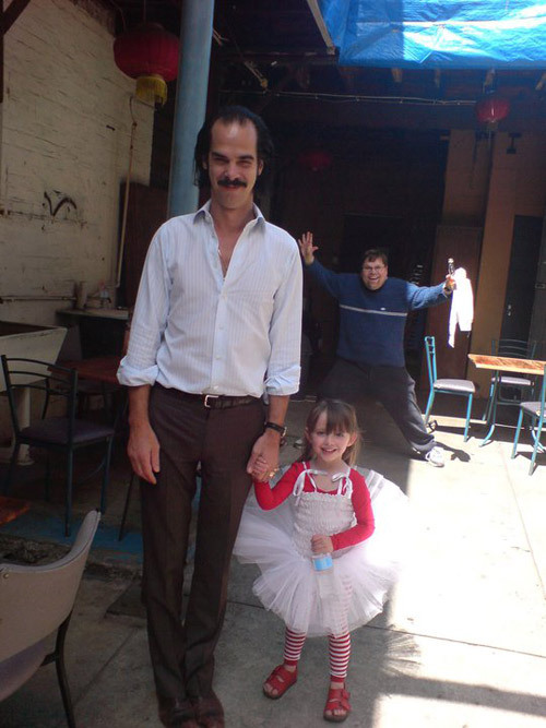 [Nick Cave holding hands with a happy little girl in a tutu and striped leggings, while a middle-aged man cavorts in the background] jonnygrawlix:  Nick Cave.