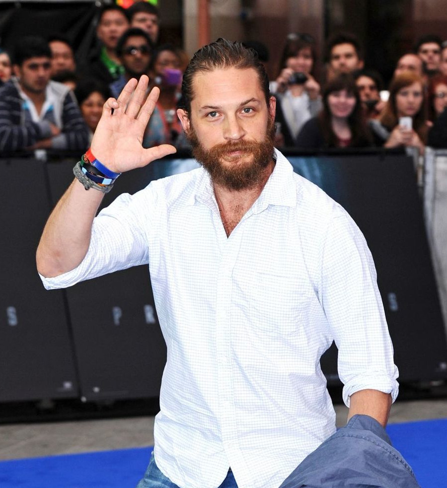 "Sexy beast — Tom Hardy hits 'em where it hurts as Hollywood's hottest new tough guy For the past few years, the movie biz has been desperately searching for that next square-jawed, powerful leading man, as greats like Clint Eastwood aged out of roles, and '80s icons, such as Sylvester Stallone, became more hammy than hot. They stripped off his shirt and served us doe-eyed Jake Gyllenhaal in ""The Prince of Persia."" They laughably tried foisting Taylor Lautner on us in ""Abduction."" Step aside, wusses. Tom Hardy is here to toss you one-handed through a plate-glass window. In just a few short years, the 34-year-old English actor has become the go-to guy for brutish, physically imposing parts. He's also become quite the sexy pin-up, if you're so inclined. This is a guy who did 2,500 push-ups a day for five weeks to bulk up for his role as England's most notorious convict in 2008's ""Bronson,"" a guy who stalks around every movie looking like he might at any second decide to uncoil a sledgehammer punch. A guy who basically owns every scene he's in through sheer strength and charisma. ""Initially I took on these kinds of roles [like Tommy Conlon, Heathcliff or Bane] to make a noise,"" Hardy told the UK's Telegraph. ""No one's ever sat up when I've played someone nice or easy to watch."" […] Runty LaBeouf has admitted that playing kin to ""big boy"" Hardy was intimidating. ""Standing next to him, I felt like Josh Groban — meek,"" he joked on ""The Tonight Show."" But Hardy is not all muscles and violence, says ""Lawless"" director John Hillcoat. ""The most interesting thing about him is the contradictions,"" he says. ""He has this masculinity to him, physically, but there's this real feminine side to him. He has these large lips. There's a softness underneath it all."" Hardy wanted that softness to translate to his ""Lawless"" character. The actor saw Forrest, the eldest brother, as a matriarchal figure. He modeled the character on Granny, the owner of Tweety from the ""Looney Tunes"" cartoons, who goes from knitting to a sudden burst of violence. He even suggested a scene in which his character darns socks, but Hillcoat nixed the idea. […] ""You think of Michael Fassbender and Jeremy Renner and Ryan Gosling. There's a whole bunch of these newer guys who are breaking in who play complex characters underneath these very masculine characters,"" Hillcoat says. ""Tom is part of that. He's looking for [a career of the] Gary Oldman or Daniel Day-Lewis variety."" And Hollywood, if you know what's good for you, you best give him one."