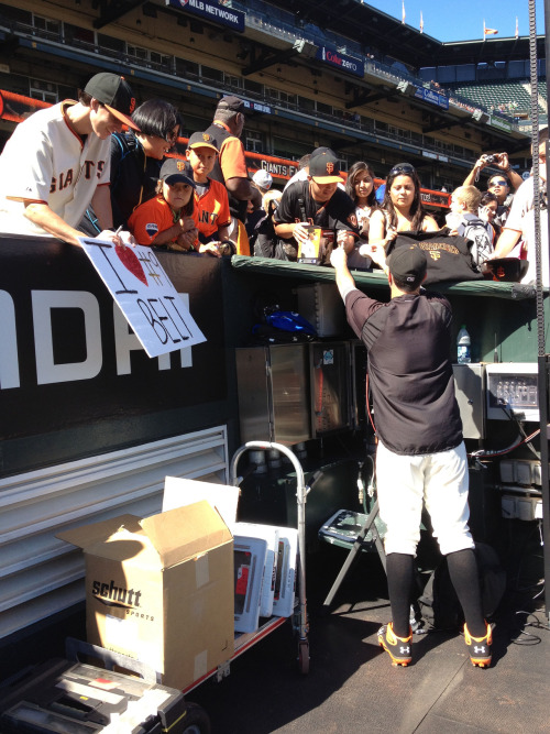 Brandon Belt signs autographs for fans before tonight's game.
