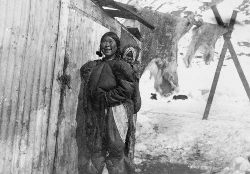 Inuit woman and child outside wood buildings. Skins hanging in background. Credit: J.E. Bernier / Library and Archives Canada / C-000744   Additional name(s): Photographer:George Lancefield?  Additional information:(Bernier Expedition 1906-07 Signatures and inscriptions: Esquimau woman and child Source