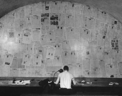 A student writing a story for the Yale university paper, facing a wall covered with front pages of papers past, 1942. -John Phillips