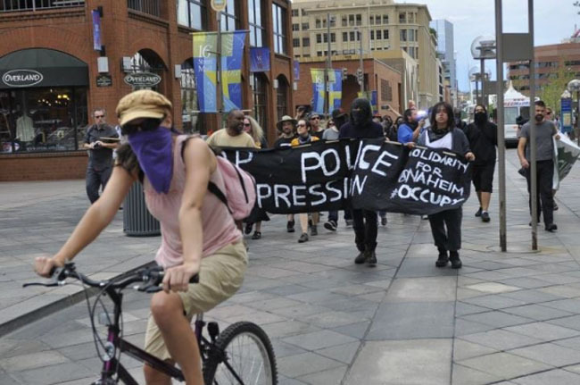 "Denver police use intimidation to try to squash an anti-police-brutality march in solidarity with Anaheim, causing some arrests:  Sergeant Andrejasich barked at us that ""if you go in the street again, we will arrest you.""  This threat seemed absurd given that whenever we march, DPD's vehicles that follow us essentially shut down traffic anyway.   Sergeant Andrejasich was clearly hoping that by threatening arrest and possible violence, he could frighten our solidarity march into giving up and going home.   He should know by now that Occupy Denver doesn't play like that.  Having seen DPD use violence or the threat of violence countless times to attempt to silence dissent, I figured someone should resolve Sergeant Andrejasich's confusion about the relationship between his department and our subversive assembly."