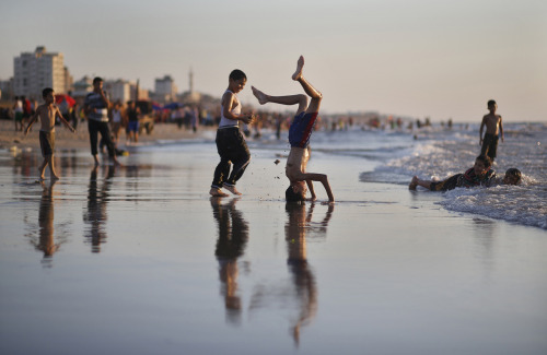 Photo of the Day: Palestinian boys play on a beach in Gaza City on a summer's day. (REUTERS/Mohammed Salem)