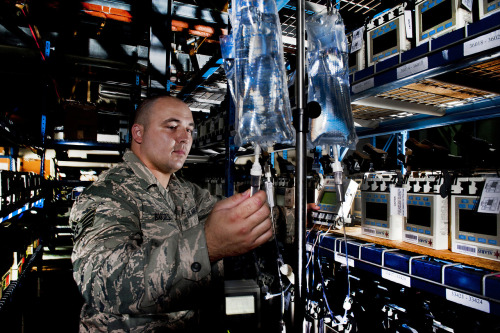 U.S. Air Force Staff Sgt. Erick Bartels uses an Alaris Medsystem III infusion pump to check the flow of liquid on lines of IV bags at Joint Base Andrews, Md., Aug. 15, 2011. Bartels is a biomedical equipment technician assigned to the Medical Logistics Flight of the 779th Medical Support Squadron.  U.S. Air Force photo by Val Gempis