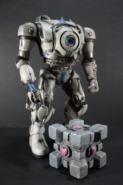 Kodykoala's Wheatley Body Atlas and P-body both have bodies and can walk around, where as Wheatley never really had the ability to walk around on his own. Here is what I think his body would look like if he were in charge of making it. I tried to stay true to the color schemes, and I even made a companion cube to go with him. I used a Wheatley key chain, Cleatus torso, and Stel arms and legs. The gun was sculpted from scratch. Wheatley is removable and the light still works, so you can still turn him on.