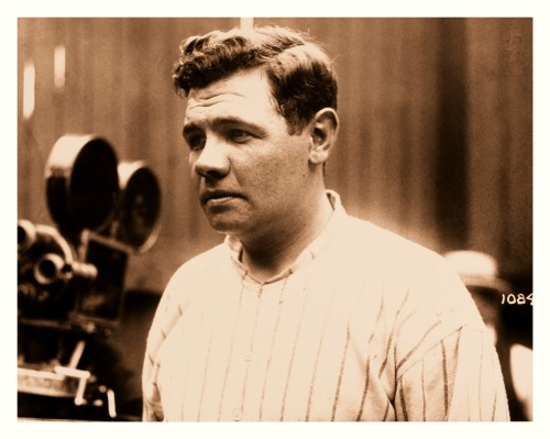 "Young Babe Ruth Readies For the Camera - 1920  The movie camera and wooden fence in the background indicate that this might be a photo taken during spring training. The ""1084"" code number on the right looks like a still image marker from a studio…yet it doesn't seem to be from ""Headin' Home"". If it were during the movie shoot, he'd be in heavy makeup and not wearing the Yankee pinstripes. Although uncredited (and Babe is essentially not posed), it looks like this picture may have been snapped by famed baseball photographer Paul Thompson."