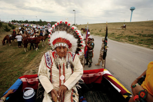 In 2006 Oliver Red Cloud, now 94 years old, sits in the back of the pickup leading the annual Oglala Nation Pow Wow parade in Pine Ridge, South Dakota. Photograph by Aaron Huey. Seen in National Geographic Magazine August 2012 cover story In the Shadow of Wounded Knee. www.aaronhuey.com