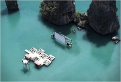 "Awe-inspiring: Floating Cinema. ""This amazing scenery is in the rocky shoreline of Yao Noi, Thailand. The Archipelago Cinema is part of the event organized by Film on the Rocks Yao Noi, a new film festival curated by Apichatpong Weerasethakul and Tilda Swinton. The auditorium raft was designed by German-born and Beijing-based architect Ole Scheeren, it was built using recycled materials. The guests are taken to the awe-inspiring glowing raft by boat, in the middle of the quiet waters of Nai Pi Lae lagoon on Kudu Island."""
