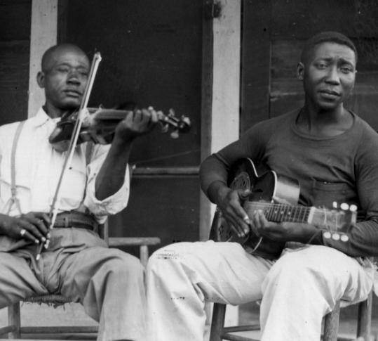 tekena:  Young muddy  Next to Muddy is Henry Sims. Photo is circa 1943.