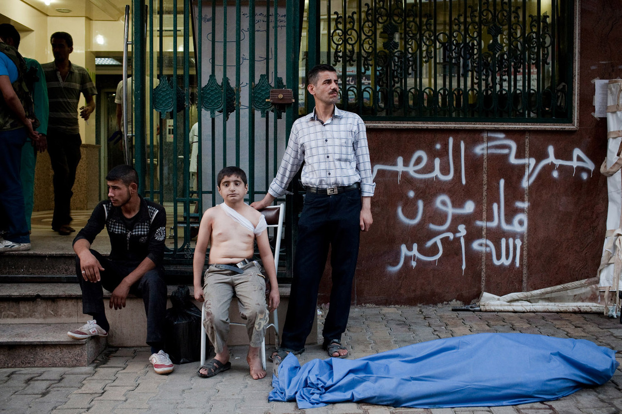 Aug. 24, 2012. Ahmed, 12, waits with his uncle (right) near the body of his father, killed by a shell in Sha'ar. Ahmed, who saw his father die, was also wounded in his back by shrapnel. Photographer Nicole Tung documents Aleppo's overburdened hospitals and the continued casualties of the ongoing Syrian civil war.  See more photos here.