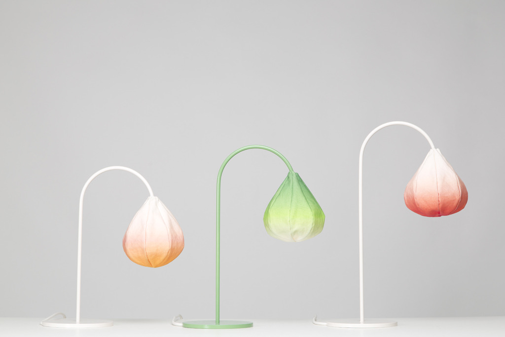 Bloom by Kristine Five Melvær. Bloom is a series of three table lamps inspired by forms from the nature. Like big drops, the shades may be associated with buds, fruits or water, while the seams in the construction are reminiscent of fibers. The steel structures have different heights, which contribute to the association of organic bodies.  Materials: Welded steel structure, printed canvas.