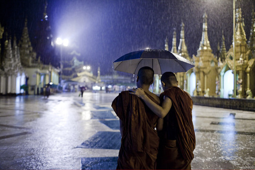 A pair of novice monks share an umbrella. The Shwedagon Pagoda is one of the holiest sites of Buddhism .Photograph: Ed Giles/Getty Images (via Photojournalist Ed Giles explores the new Burma – in pictures | Art and design | guardian.co.uk)