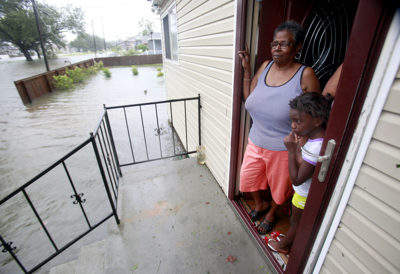Lessie Lewis stands on the front porch with her granddaugher Kodi Lewis, 6, as flood waters surround their home on St. Roch ave. as Hurricane Isaac makes land fall in New Orleans, Louisiana August 29, 2012. [REUTERS/Sean Gardner] LIVE COVERAGE: Hurricane Isaac slams Louisiana