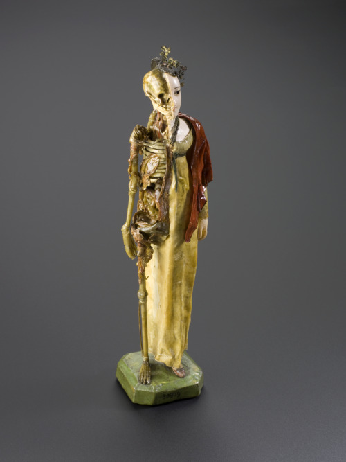 catafalques:  Coloured wax model of a female, half skeletal, half living and dressed in regency clothing, England, 1810-1850: This lady is dressed in Regency clothing typical of the first half of the 1800s. She is skilfully created out of wax. She is half woman, half skeleton. The statue may have been made for one of three reasons: a darkly comic novelty, a 'memento mori' (a reminder of death), or a teaching aid. She is paired with a separate male statue (A78827). These two examples of regency waxwork were exhibited in Montreal, Canada at the International and Universal Exposition in 1967.