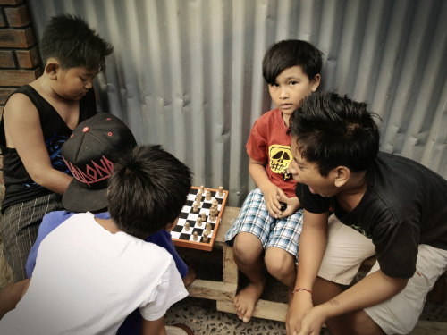 Local kids from Bali, play chess on the corner of the street in old city Kuta, Bali, Indonesia. © Ethan Knight. Shot with the 3RDi Kit - www.get3rdi.com