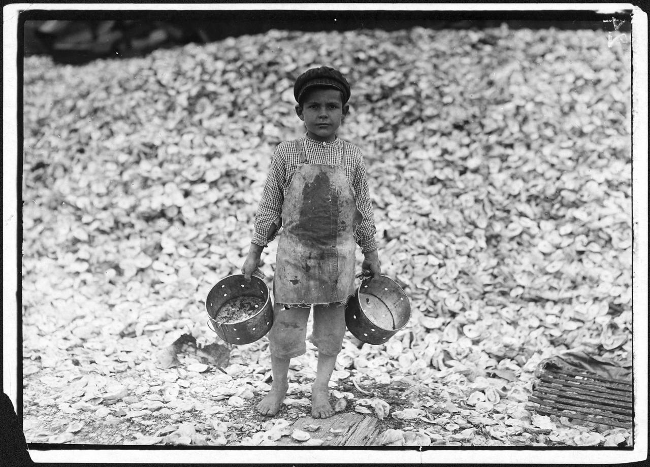 "Image description: A five-year-old child laborer named Manuel stands before a mountain of oyster shells in Biloxi, Mississippi in 1912. This image was part of a series of 5,000 photographs taken by Lewis Hine for the National Child Labor Committee. They were used by the Department of Commerce and Labor's Children's Bureau in both its investigations of child labor issues and advocacy for federal legislation to limit workplace abuses against children. Hines took pictures of children working as harvesters in agricultural field work; pickers in seafood, vegetable, and fruit canneries; workers in cotton mills and glass, furniture, and cigar factories; as ""breaker boys"" in coal mines; and more. Image courtesy of the National Archives and Records Administration."