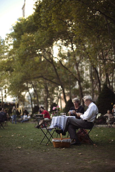"jamesnord:  I saw this couple last night in Bryant Park and asked them if I could snap their photo. After showing them the results, I sat down for a chat. The first leaves were shaking themselves off the trees in the strong breeze and I asked what the occasion for their picturesque picnic was figuring an anniversary or birthday. The man put his cards down and smiled at me saying, ""I have been married to the best girl in the world for 30 years, I am doing my best to make sure she knows that."""
