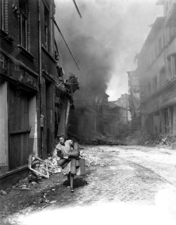 itsjohnsen:  A German woman carrying her possessions runs from the burning city of Seigburg, 1945. Troy A. Peters
