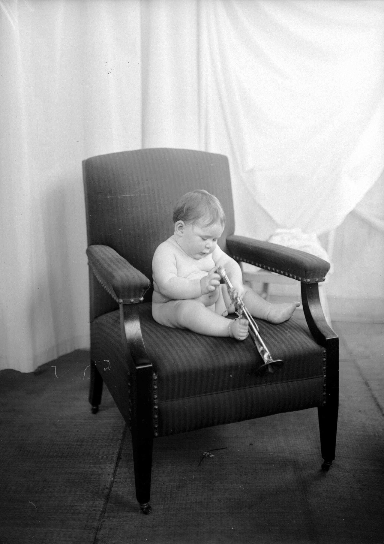 "Better Baby Contestant, ca. 1920 The Better Baby Contest was held at the Vancouver Exhibition (PNE) from 1913 to 1919. From there it moved to New Westminster and was a staple until the exhibition buildings there burned down in 1929. The contests were initiated by the Local Council of Women and the babies were judged by medical doctors, who deducted points for any defects they found. So-called defects could be as trivial as moles or pug-noses, and would stigmatize children as ""flawed"" for the rest of their lives. Locals often became indignant when their babies were judged to be above the ideal weight for their age. Criteria were set in the east, whereas BC babies tended to be more robust because of their rugged frontier lifestyle, they argued, and therefore shouldn't be penalized.   These were not just beauty contests, but rather were intended to educate the public. The Better Baby Contests fit into the larger eugenics movement that included such things as forced sterilization of the ""feeble minded."" Naturally, only Anglo-Saxon babies were entered in the contests, since one of the main driving forces of eugenics was that miscegenation and non-British immigration would ultimately result in ""race suicide"" for North American whites. For more info, see Gerald E Thomson, ""'A Baby Show Means Work in the Hardest Sense': The Better Baby Contests of the Vancouver and New Westminster Local Councils of Women, 1913-1929,"" BC Studies no. 28, Winter 2000/2001 Source: Photo by Stuart Thomson, City of Vancouver Archives #99-1297"