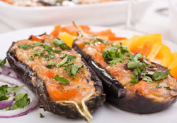 "STUFFED EGGPLANT In a frying pan or a wok, stir fry the onion and tomato with the garlic in a little olive oil. Add the minced beef and keep stirring well. Reduce the heat.2 large eggplant600g good quality minced beef1 medium tomato2 small onions, thinly chopped2 cloves garlic, crushedFresh rosemary, fresh thymeExtra virgin olive oil Meanwhile, cut open the eggplant in half lengthwise and empty with a spoon, making sure you keep about 1/2 inch flesh on the skin to make the ""shells"". Thinly slice the flesh you have just been taking out and add it to the stir fry. Add some salt and some fresh rosemary and thyme (or any herb you may fancy). Once the meat and eggplant are thoroughly cooked, remove from the heat and stuff the mixture in the shells. Place them in an ovenproof dish and bake for 45 minutes at 350F."