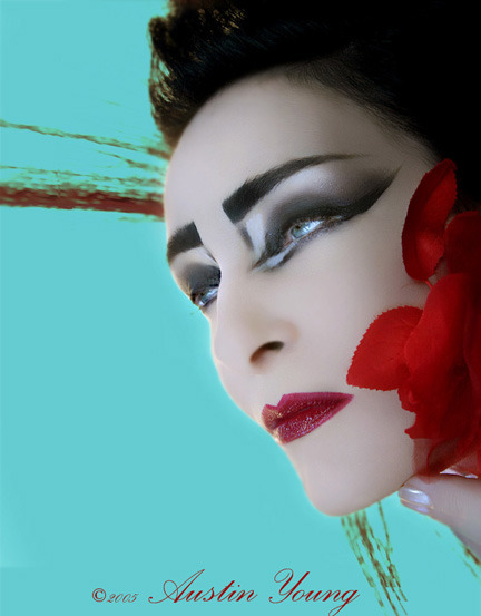 [Closeup color photo of Siouxsie against an aqua background, face partially obscured by brilliant red-orange leaves.  Photo by Austin Young.]