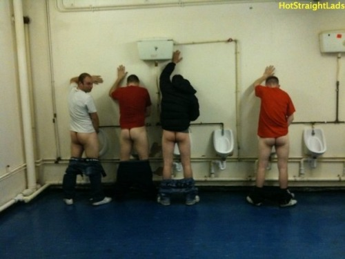 4 hot straight lads, taking a piss in a public bathroom with their pants down to their ankles.
