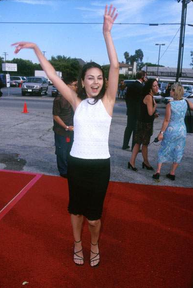 Mila Kunis waves her arms about at the 1999 Teen Choice Awards.