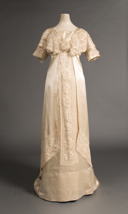Wedding dress worn by Mary Peterson Wells, 1910-11 (worn in) the Philippines (Manila), FIDM Museum & Galleries   Wedding dresses usually follow the lines of contemporary fashionable dress. This wedding gown, with its high waist and slim silhouette, highlights the popularity of silhouettes inspired by ancient Greek and Roman dress. As described in a post featuring a c. 1912 tunic dress, this style emerged about 1908 and was a dramatic departure from the S-bend silhouette. Mary wore this wedding dress with a headpiece of wax orange blossoms and buds. Sweet-smelling orange blossoms have long been worn by brides, but their popularity was cemented in 1840, when Queen Victoria wore a crown of orange blossoms for her wedding. For those without access to fresh orange blossoms, wax blossoms were a popular alternative. In this photograph, Mary is pictured wearing her wedding gown, the orange blossom headpiece, an extended veil and long gloves. Though we know that this gown was worn for a wedding in the Philippines, we don't know where it was made. If made in the Philippines, its up-to-date style is testament to the rapid spread of fashion information to regions far from Paris, the center of high fashion. Alternately, the bride might have commissioned the gown in the United States before setting sail for Manila. Answering this question will take more time, as we haven't completed our research on Mary Peterson Wells. We know that she was born in 1887, but not the location of her birth. Based on what we've discovered so far, she was probably related to James Jackson Peterson. Born in West Virginia in 1853, Peterson was appointed United States consul for Honduras in 1890. By the early 20th century, Peterson had moved to Manila where he received an appointment as official translator and sheriff for the City of Manila. The relationship between James Jackson Peterson and Mary Peterson Wells is still unclear. The lace panels decorating the gown might have been a family heirloom, given to Mary for use on her wedding dress.