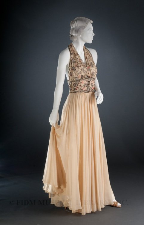 "oldrags:  REBLOG BECAUSE IT'S BEAUTIFUL!! Evening dress by Madeleine ""Madame"" Vionnet, 1936-38 France, FIDM Museum & Galleries  French couturier Madeleine Vionnet was born on [June 22] in 1876. Born in Chilleurs-aux-Bois, about 75 miles from Paris, Vionnet was apprenticed to a local dressmaker at age 11. She spent several years in this first apprenticeship, moving to a small design house in Paris when she was 17. She later worked in London for several years, returning to Paris by 1901, where she worked first for Callot Soeurs and later for Doucet. In 1912, Vionnet opened her own salon, but closed the business at the beginning of World War I in 1914. After spending the war years in Italy, Vionnet returned to Paris and re-opened her couture house in 1918. Though Vionnet began her training in the late 19th century, when artifice and decoration were the foundations of fashion, she developed a startlingly modern, deceptively simple approach to design. Many of her garments were based on simple geometric forms; square, circle or rectangle. The bias cut was integral to her work, and largely eliminated the need for shaping darts. Vionnet disliked corsets, and designed her garments to be worn without this confining undergarment. House models were encouraged to go without undergarments during fittings. Vionnet's primary concern was the form of a garment and how the garment related to the body. Working on her legendary wooden mannequin, Vionnet draped, cut, and slashed plain muslin toiles until a satisfactory design emerged. A suitable textile was chosen only after the design was complete. Vionnet herself tended towards neutrals, as she acknowledged in a 1937 interview: ""I like black and white. They are pure color. Next to them, I like natural colors like the blue and green of eyes and red of lips.""1 In lieu of color, Vionnet often created textural contrasts by using different sides of the same fabric, or by pairing different textures in the same garment. If a patterned or brightly colored textile appeared in a Vionnet design, it was probably selected by Marcelle Chaumont, the premiѐre of Vionnet's atelier. Chaumont's color sense mediated Vionnet's taste for neutrals. Though Vionnet may have been most concerned with form, many of her garments feature sophisticated, carefully placed embellishment. Aware that her creative strength was in dressmaking, not surface design, Vionnet hired designers to create patterns for textile and surface decoration. From 1919 to 1925, she worked closely with Thayaht. In addition to creating surface designs for Vionnet, he illustrated her garments for the French fashion journal La Gazette du Bon Ton. In 1918, Vionnet hired Marie-Louise Favot. A dressmaker and trained artist, Favot (nicknamed Yo because Vionnet already employed another Marie-Louise) designed all of Vionnet's embroidery motifs. Though the motifs were designed in-house, the actual work was contracted out to Michonet, a Parisian embroidery firm founded in 1858. Because so many of Vionnet's designs were cut on the bias, innovative techniques were used to apply surface decoration. For example, embroidery stitches were angled to follow the grain of the bias-cut fabric so as not to interfere with the drape. Yo worked particularly closely with one Michonet embroiderer, Albert Lesage. (Hopefully this name rings a bell!) Lesage purchased Michonet in 1922, changing the name of the firm to Lesage. Soon afterwards, Albert Lesage and Yo were married. Their son, Francois Lesage, ran the house from 1949 until he passed away in December 2011. Today, the firm produces both private commissions and designs for ready-to-wear and haute couture. Given what we know about Vionnet's atelier, Yo probably designed the bodice embroidery, which was then executed by Lesage's embroiders. The chiffon foundation is embroidered with silk and metallic thread in a pattern of twining vines and flowers, accented with rhinestones and glass cabochons. Looking beyond the lovely surface embellishment, Vionnet's construction techniques are evident in the unstructured bodice. Instead of using bust darts for shaping, the fabric is gathered and twisted around the neck; this technique pulls the fabric close to the body, ensuring a close fit without the use of darts. The wearer's back is left nearly bare, accented by embroidered straps. A cummerbund wraps around the waist, compressing the excess chiffon into soft gathers."